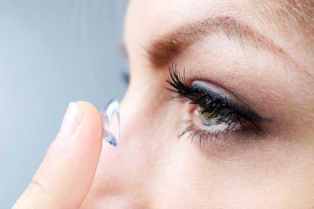 Жінка надягає контактні лінзи - фото